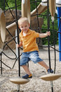 Cute boy enjoys sunny day at the playground. Royalty Free Stock Photo