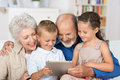 Cute boy and girl looking at a pc tablet sitting in the lap of their grandmother grandfather all Stock Photos