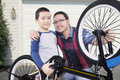 Cute boy and his father repairing bicycle portrait of little dad smiling at the camera after a at the garage Stock Image