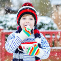 Cute boy holding big cup and hot chocolate drink and marshmallo Royalty Free Stock Photo