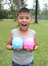 Cute boy holding piggy bank young blue and pink with green grass background Royalty Free Stock Images