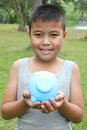 Cute boy holding piggy bank young blue and pink with green grass background Stock Images