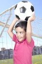 Cute boy holding a soccer ball over his head Royalty Free Stock Photo