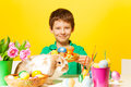 Cute boy holds plate with eastern eggs and rabbit sitting on the table the yellow background Royalty Free Stock Photo