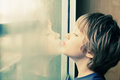 Cute boy looking through the window Royalty Free Stock Photo
