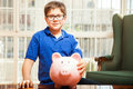 Cute boy with a piggy bank little kid glasses holding all of his savings in at home Royalty Free Stock Image