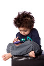 Cute boy playing games on mobile device toddler sitting and crazy hair isolated Royalty Free Stock Image