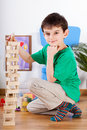 Cute boy playing at preschool little with tower of blocks Stock Photo