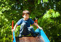 Cute boy playing on slide against green trees background Royalty Free Stock Images