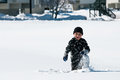 Cute boy playing in the snow adorable little kneeling Stock Photography