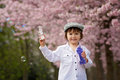 Cute boy, playing with soap bubbles in a cherry blossom tree gar Royalty Free Stock Photo