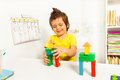 Cute boy putting blocks replicating example colorful wooden in construction sequence sitting at the table in classroom Royalty Free Stock Photo