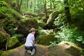 Cute boy on the rocks near a scenic waterfall playing Royalty Free Stock Images