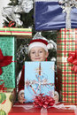 Cute Boy In Santa Hat Surrounded By Gift Boxes Stock Images