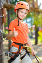 Cute boy shows thumb up with climbing equipment in Royalty Free Stock Photo