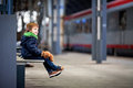 Cute boy, sitting on a bench with teddy bear, looking at a train