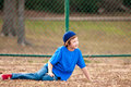 Cute boy sitting on grass playing backyard baseball Stock Photography