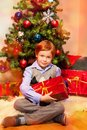 Cute boy sitting near Christmas tree Stock Photo