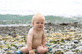 Cute by boy sitting on the stony beach. Funny toddler on the seashore looking at camera Royalty Free Stock Photo