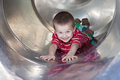 Cute boy sliding down the slide smiling at camera Stock Photo