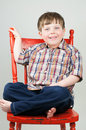 Cute boy smiling on orange chair adorable blue eyed in plaid shirt smiles rustic wooden Stock Photos