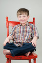 Cute boy smiling on orange chair adorable blue eyed in plaid shirt smiles rustic wooden Stock Images