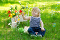 Cute boy and soap bubbles adorable little sitting on the green grass with his eyes closed surrounded with flowers Stock Photos