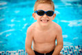 Cute boy in sunglasses sitting at pool little swimming Stock Photos