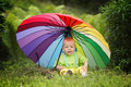 Cute boy under colorful umbrella little outdoors Royalty Free Stock Photo