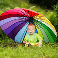 Cute boy under colorful umbrella little outdoors Stock Photos