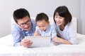 Cute boy using tablet pc with happy family Royalty Free Stock Images