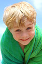 Cute boy wrapped in beach towel a blonde child up a bright smiling at the camera Stock Image