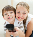 Cute brother and sister watching TV Stock Image