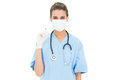 Cute brown haired nurse in blue scrubs wearing a protective mask and holding a syringe Royalty Free Stock Photo