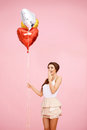 Cute brunette with balloons colorful heart shaped on pink Stock Photo