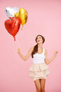 Cute brunette with balloons colorful heart shaped on pink Royalty Free Stock Photo