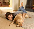 A cute brunette with a dog on a comfortable carpet Royalty Free Stock Photo