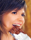 Cute brunette eats chocolate Stock Photo