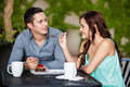 Cute brunette and her boyfriend beautiful young sharing cake with date at a coffee shop outdoors Royalty Free Stock Photography