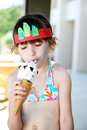 Cute brunette little girl eating ice cream in bathing suit Stock Image