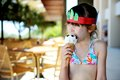 Cute brunette little girl eating ice cream in bathing suit Royalty Free Stock Images