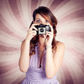 Cute brunette pinup girl surprised expression pressing shutter button old film camera taking vintage photograph Royalty Free Stock Photography