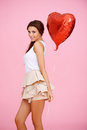 Cute brunette with red heart balloon on pink Royalty Free Stock Images