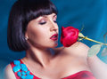 Cute brunette with red rose on blue background in studio Royalty Free Stock Photo