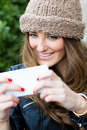 Cute brunette woman taking photo of herself portrait on the street Royalty Free Stock Photo