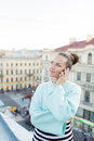 Cute businesswoman in glasses talking on phone and smiling while standing on the roof of the house in the old town Royalty Free Stock Photo