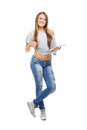 Cute casual teenage girl with digital tablet gesturing thumbs up attractive caucasian styled young teen woman in blue jeans and Stock Photo