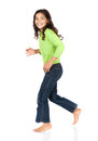 Cute caucasian girl pretty wearing a green long sleeve top and blue jeans is running and smiling at the camera Royalty Free Stock Photography