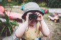 Cute Caucasian girl in yellow dress and hat looking through binoculars