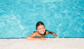 Cute charming little girl relaxing in swimming pool with closed eyes
